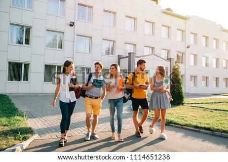 Free time of a students, bachelor`s campus life rhythm. Five friendly students are walking after they passed test outside the college building and discuss the project, smiling, enjoying, carefree Stock photo ©