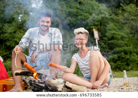 Free time on beach, young couple is baking sausages