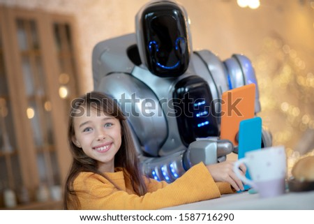 Free time .Robot with tablet and a smiling girl sitting at the kitchen having free time