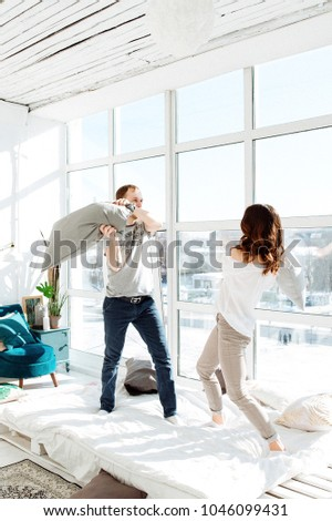 Free time together. Happy beautiful couple is spending weekend together at home, relaxing and enjoying the company of each other. man and woman fighting with pillows on the bed.