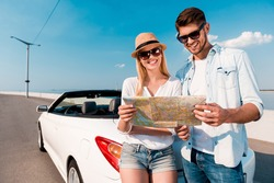 Free to choose our destinations. Joyful young couple examining map while standing against their white convertible