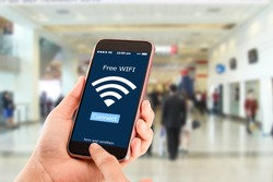 Free wi-fi concept.Hands holding mobile phone on blurred business man walking