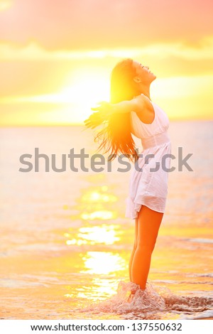 Free woman enjoying freedom feeling happy at beach at sunset Beautiful serene relaxing woman in pure happiness and elated enjoyment with arms raised outstretched up Asian Caucasian female model