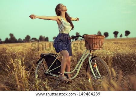 Free woman enjoying freedom on bike on wheat field at sunset