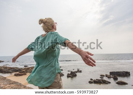 Free woman enjoying windy weather on beach on overcast day with arms raised outstretched.