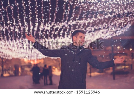 Photo of Free young man with outstretched arms looking up while being excited about winter weather at decorated city street at night, he standing under snow - Image