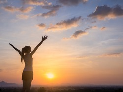 Free young woman raising arms to golden sunset. Freedom and success concept,relaxing and enjoying nature with copy space.