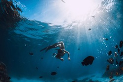 Freediver girl in bikini with fins glides underwater in blue transparent ocean