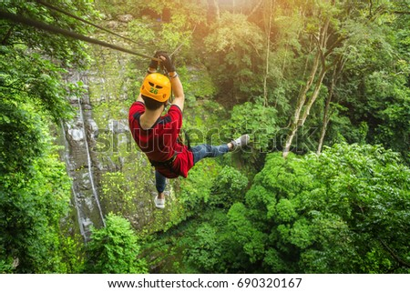 Freedom adult Man Tourist Wearing Casual Clothing On Zip Line Or Canopy Experience In Laos Rain Forest - Shutterstock ID 690320167