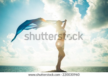 Photo of Freedom and beauty concept. Beautiful girl with blue scarf standing on the Rock. Flying. Free. Vacation