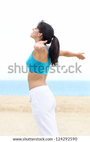 Freedom and bliss summer on beach concept. Happy young woman raising arms outstretched, feeling the breeze and breathing fresh air.