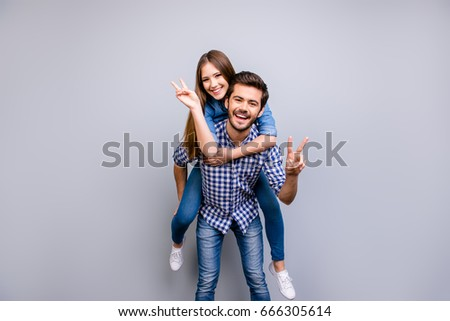 Freedom and fun, emotions and feelings. Cheerful and playful couple in casual outfits are fooling around, gesturing peace signs, smiling, posing, going crazy on pure light background