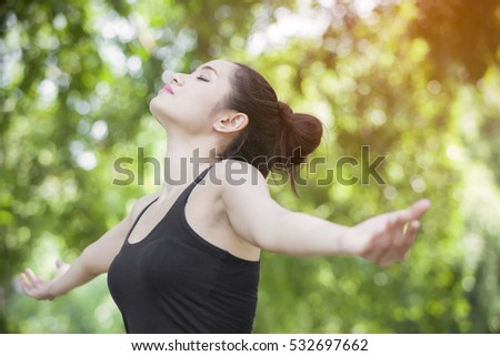 Freedom and happiness woman raise up hand and deep breath with sun lighting against green background.