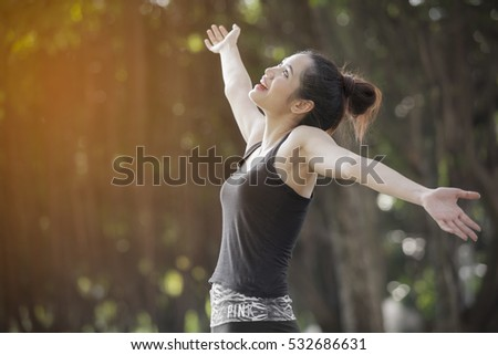 Freedom and happiness woman raise up her hand and deep breath with the sun lighting against green background.