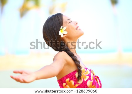 Photo of Freedom beach woman smiling happy and serene with arms outstretched in free pose. Beautiful spiritual elated happiness concept image with multicultural Asian / Caucasian female model.