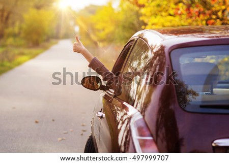Freedom car travel concept - woman relaxing out of window in a car. Girl relaxing enjoying holidays road trip #497999707