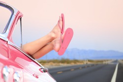 Freedom car travel concept - woman relaxing with feet out of window in cool convertible vintage car. Girl relaxing enjoying free holidays road trip.