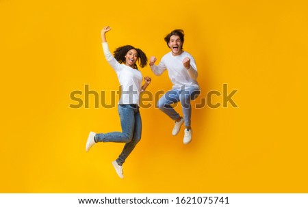 Freedom. Cheerful afro girl and handsome guy jumping in air, having fun together over yellow background, copy space