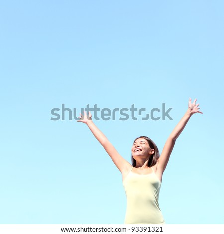 Freedom concept. Free woman smiling happy with arms raised joyful under clear blue sky. Beautiful young multiracial Asian / Caucasian girl in her 20s.