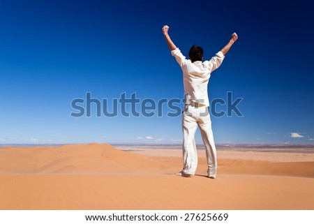 Freedom concept: Rear view of an adult white man standing on a sand dune and holding arms up. Erg Chebbi, Maroc