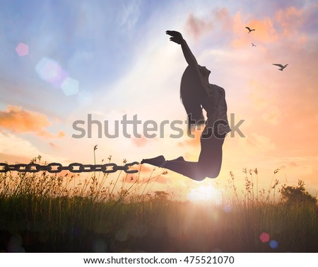 Freedom concept: Silhouette of a woman jumping and broken chains at orange meadow autumn sunset with her hands raised