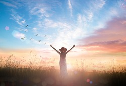 Freedom concept: Silhouette of healthy woman raised hands at meadow sunset background