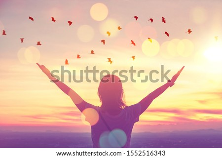 Freedom feel good and travel adventure concept. Copy space of silhouette woman rising hands on sunset sky at top of mountain and bird fly abstract background. Vintage tone filter effect color style. Foto d'archivio ©