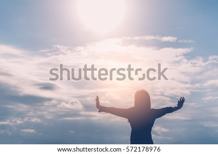 Freedom feel good and travel adventure concept. Copy space of silhouette woman rising hands on blue sky and white cloud with sun light background. Vintage tone filter effect color style.