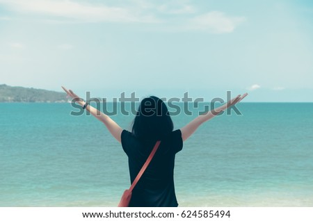 Freedom feel good and travel adventure concept. Copy space of silhouette woman rising hands with blue sky and white cloud on beach background. Vintage tone filter effect color style.