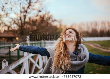 Freedom feel good. Joyful woman rising hands outside.