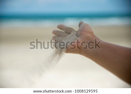Freedom hand,Let it go and Release concept.Hand let go of woman release sand on beautiful sea beach and blue water background.