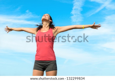 Freedom happy concept. Free woman raising arms to clear blue sky. Beautiful,  joyful and blissful caucasian girl.