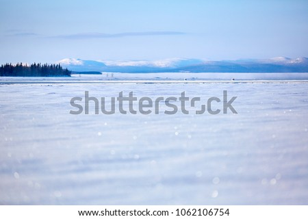 Freedom is in us. Frozen lake covered with snow, and mountain in the background and piece of tundra forest. Porjus. Sweden.
