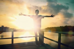 Freedom man with inspiration rise hands up and worship god in the morning sun background. Now Christian praise Jesus reborn in easter day concept for wisdom life, hope faith love