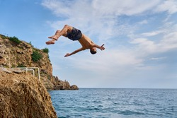 Freedom, motivation and creativity, man flipping from the scale on the beach. Young man doing a back flip into sea, Antalya, Turkey