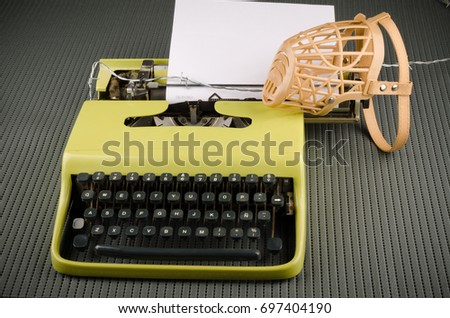 Freedom of press and speech concept using a muzzle and a vintage typewriter