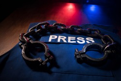 Freedom of the press and journalism concept. Blue journalist (press) vest in dark with backlight and fog. Shackles on vest. Selective focus