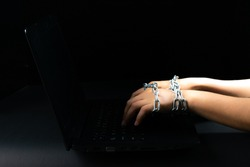 Freedom of the press and journalism, conceptual image Laptop and woman hand tied with chains can not typing keyboard on black background. World press freedom day. Copy space for advertisers.