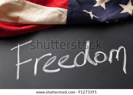 Freedom sign on a chalkboard with vintage American flag