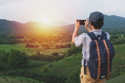 Freedom traveler man standing ,Image with sunrise  effect filte,A man carrying a bag,Using a phone to take pictures