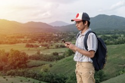 Freedom traveler man standing ,Image with sunrise  effect filte,A man carrying a bag,Using  phone,copy space