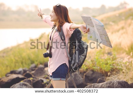 Freedom traveler woman standing with raised arms and enjoying a beautiful nature