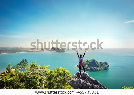 Freedom traveler woman standing with raised arms on the top of mountain at Khao Lom Muak and enjoy the beautiful of seascape, travel, freedom, Thailand.