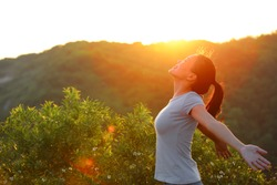 Freedom woman open arms at sunrise mountain peak wellness concept