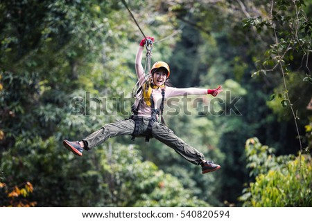 Freedom Woman Tourist Wearing Casual Clothing On Zip Line Or Canopy Experience In Laos Rainforest, Asia