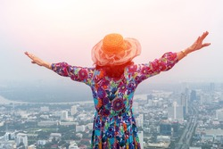 Freedon Beautiful Asia old woman standing on skyscaper building looking scenic view. People travel concept.