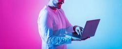 Freelance and work remotely, online game and correspondence. Contented millennial guy use laptop and holds in hands on pink and blue background, panorama, copy space