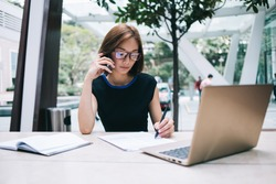 freelance Asian female in black formal wear and eyeglasses sitting at table with notepad holding pen having phone call while using laptop working remotely in workplace on background of glass wall