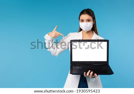 Freelance. Busineswoman wearing protective mask, showing forefinger to laptop computer with a blank white screen,Concept of prevention of the spread of COVID-19 virus and network ad