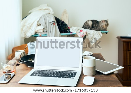 Freelance Desk with laptop in mess at home apartment. Quarantine, self-isolation, sociophobia. Online learning, teleworking, online lectures. Concept of digital nomads, home office Stock photo ©